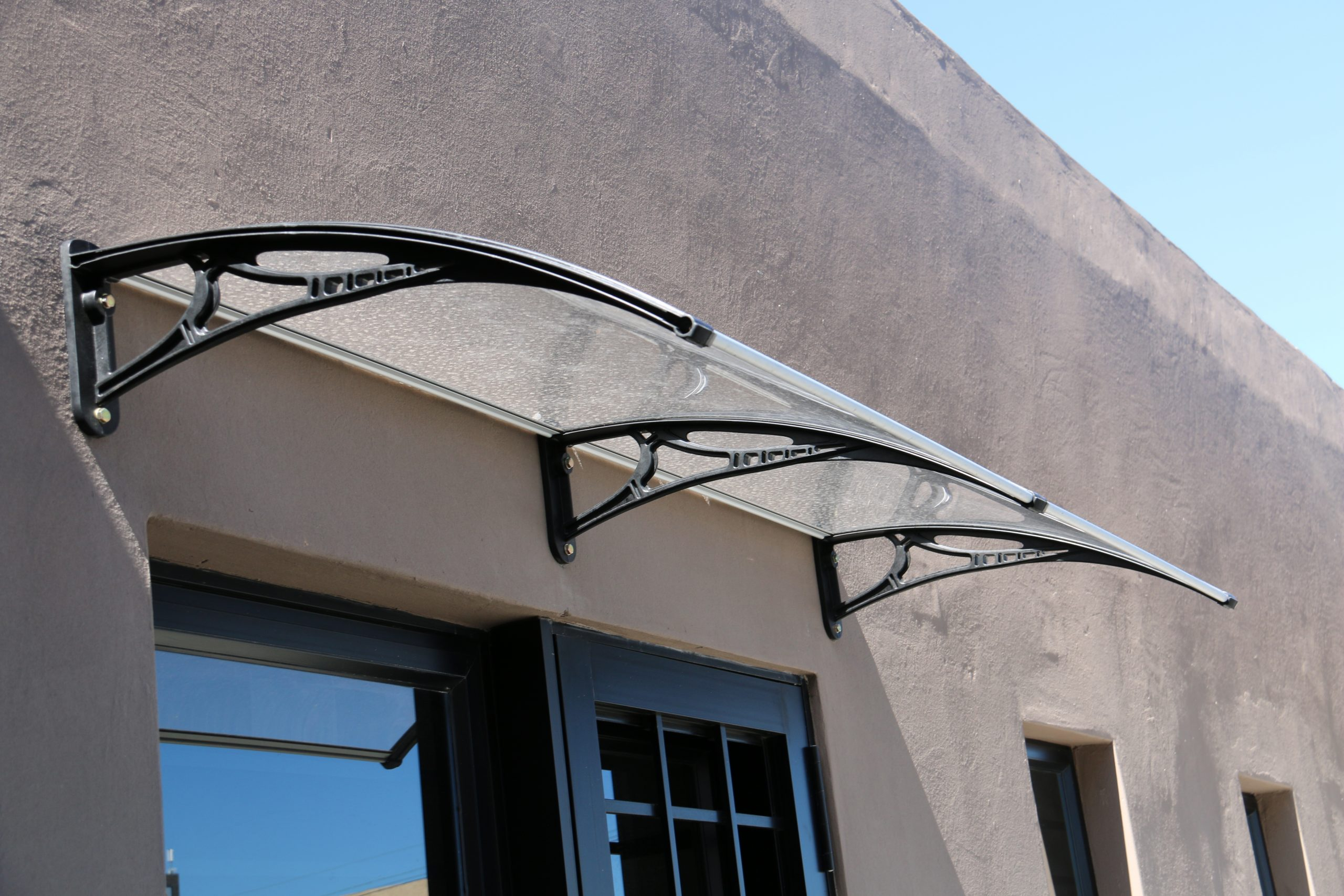 Acrylic awning protecting windows